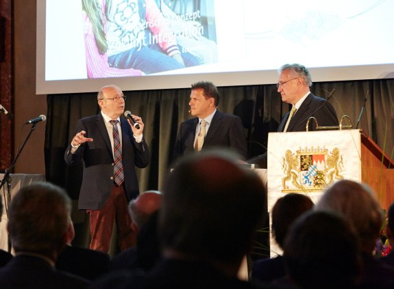 Drei Männer stehen auf der Bühne, einer spricht in ein Mikrofon.
