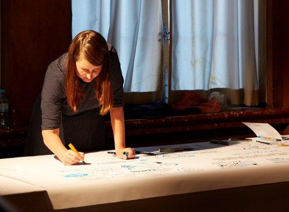 Frau zeichnet über einen Tisch gebeugt.