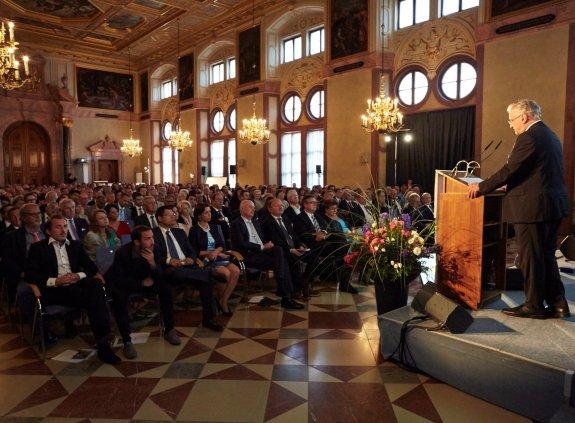Blick von vorne ins Publikum, rechts Bühne mit Joachim Herrman am Rednerpult