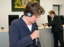 Emilia Müller im Sitzungssaal mit Kopfhörern, spricht in ein Mikrofon.