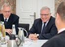 Sozialsstaatssekretär Hintersberger unterhält sich am Konferenztisch mit mit Mitgliedern der Geschäftsleitung und Führungsebene der BayernLabo