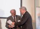 Sozialstaatssekretär Johannes Hinterberger überreicht Heinz Brehm eine Urkunde und Pralinen.