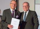 Sozialstaatssekretär Johannes Hinterberger steht neben Peter Held, der eine Urkunde hält.