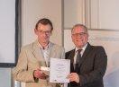 Sozialstaatssekretär Johannes Hinterberger steht neben Klaus Koch. Sie halten zusammen eine Urkunde.