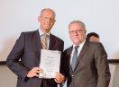 Sozialstaatssekretär Johannes Hinterberger steht neben Wolfgang Böhm, der eine Urkunde hält.