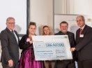 """Drei Personen halten einen Förderscheck mit der Aufschrift """"186.927 Euro"""". Daneben stehen rechts Sozialstaatssekretär Johannes Hintersberger und links Dr. Thomas Bauer, Regierungspräsident von Mittelfranken."""