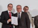Sozialstaatssekretär Johannes Hinterberger steht neben Jörg Schlag, der eine Urkunde hält.