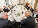 """Sozialstaatssekretär Johannes Hintersberger sitzt am Konferenztisch mit Mitgliedern der Geschäftsleitung und Führungsebene der BayernLabo und hält das Signet """"Bayern barrierefrei"""""""