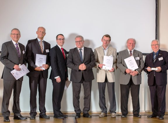 Sechs geehrte Ehrenamtliche stehen mit ihren Urkunden um Sozialstaatssekretär Johannes Hintersberger herum auf der Bühne.