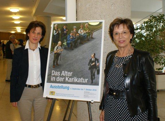 Sozialstaatsministerin Emilia Müller und Dr. Franziska Polanski, Initiatorin und Kuratorin der Ausstellung, stehen neben einem Aufsteller mit dem Plakat zur Ausstellung.