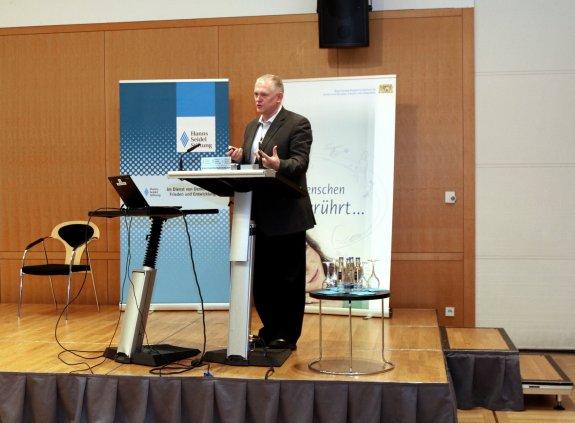 Professor Piotr Krakowiak steht am Rednerpult auf der Bühne