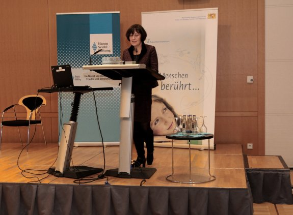 Professorin Martina Wegner steht am Rednerpult auf der Bühne