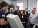 Ministerin Emilia Müller spricht mit einem Auszubildenden, darum herum stehen weitere Männer