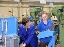 Eine Auszubildende und Ministerin Emilia Müller stehen an einem Schaltpult und bedienen es