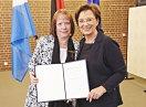 Staatsministerin Emilia Müller und Margot Albert halten die Urkunde in die Kamera