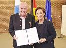 Staatsministerin Emilia Müller und Wilhelm Wachinger halten die Urkunde in die Kamera