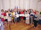 Gruppenbild von Sozialministerin Emilia Müller mit allen Ausgezeichneten, die die Urkunden und Medaillen halten