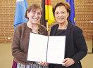 Staatsministerin Emilia Müller und Magdalena Avenius halten die Urkunde in die Kamera