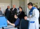 Ein Auszubildender sitzt an einer Maschine und bedient diese, Ministerin Müller sowie weitere Personen schauen zu