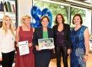 Staatsministerin Emilia Müller mit Preisträgerinnen die eine Urkunde halten