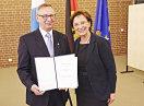 Staatsministerin Emilia Müller und Matthias Meyer halten die Urkunde in die Kamera