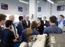 Ministerin Müller unterhält sich im Kreis von Mitarbeitern und Auszubildenen in einer Werkhalle