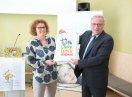 Staatsekretär Johannes Hintersberger und Susanne Puhle halten eine Tasche mit dem Logo der Kampagne in die Kamera