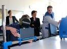 Ein Auszubildender und ein Mitarbeiter bedienen eine Lötmaschine, Ministerin Müller sowie weitere Personen schauen zu