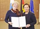 Staatsministerin Emilia Müller und Hanna Hermann halten die Urkunde in die Kamera