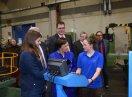 Eine Auszubildende steht mit Ministerin Emilia Müller an einem Schaltpult, darum herum stehen weitere Personen