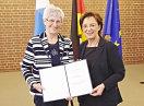 Staatsministerin Emilia Müller und Rita Pfauntsch halten die Urkunde in die Kamera