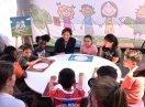 Emilia Müller sitzt mit Kindern an einem runden Tisch und unterhält sich mit ihnen
