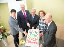 Staatsekretär Johannes Hintersberger schneidet eine Torte mit dem Kampagnenlogo an, neben ihm stehen weitere Männer und eine Frau