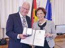 Der Ausgezeichnete mit Bayerns Sozialministerin Emilia Müller, beide halten eine Urkunde und die Medaille in die Kamera
