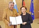 Staatsministerin Emilia Müller und Theodor Seeor halten die Urkunde in die Kamera