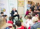 Staatsekretär Johannes Hintersberger sitzt auf einem Stuhl und liest Kindern, die im Halbkreis um ihn sitzen, vor.