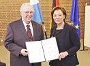 Staatsministerin Emilia Müller und Albin Hüttl halten die Urkunde in die Kamera