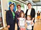 Staatsministerin Emilia Müller mit Preisträgerinnen und Kindern, die eine Urkunde halten