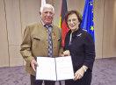 Franz Erras und Staatsministerin Emilia Müller halten eine Urkunde in die Kamera