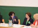 Frau Ostner spricht in ein Mikrofon. Die anderen Diskussionsteilnehmerinnen sitzen daneben und hören zu.