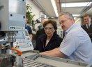 Staatsministerin Emilia Müller und ein Mann stehen am Schaltpult einer Maschine