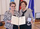 Die Ausgezeichnete mit Bayerns Sozialministerin Emilia Müller, beide halten eine Urkunde und die Medaille in die Kamera