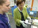 Staatsministerin Emilia Müller an einer Maschine, sie trägt Schutzhandschuhe. Eine Auszubildende steht neben ihr und erklärt.