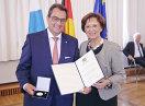 14 StaDer Ausgezeichnete mit Bayerns Sozialministerin Emilia Müller, beide halten eine Urkunde und die Medaille in die Kamera