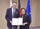 Christoph Franzeck und Staatsministerin Emilia Müller halten eine Urkunde in die Kamera