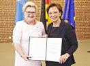 Staatsministerin Emilia Müller und Pia Dohn halten die Urkunde in die Kamera