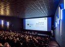 Blick über voll besetzten Kinosaal auf die Leinwand