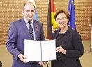 Staatsministerin Emilia Müller und Christoph Freundl halten die Urkunde in die Kamera