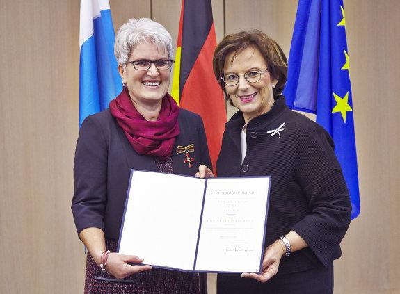 Irene Schiessl und Staatsministerin Emilia Müller halten eine Urkunde in die Kamera