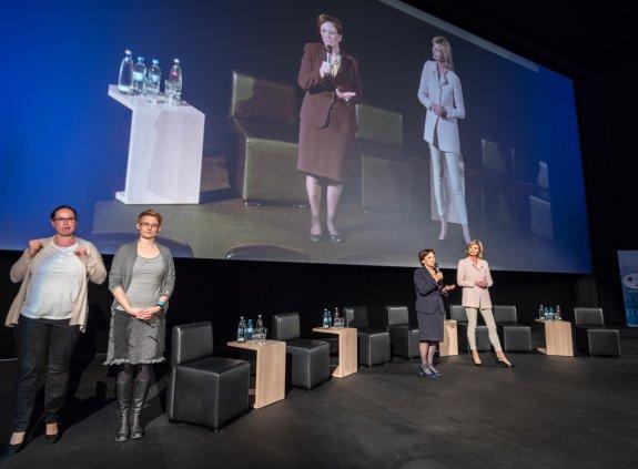 Emilia Müller und Moderatorin Anouschka Horn auf der Bühne, links zwei Gebärdensprachdolmetscherinnen.